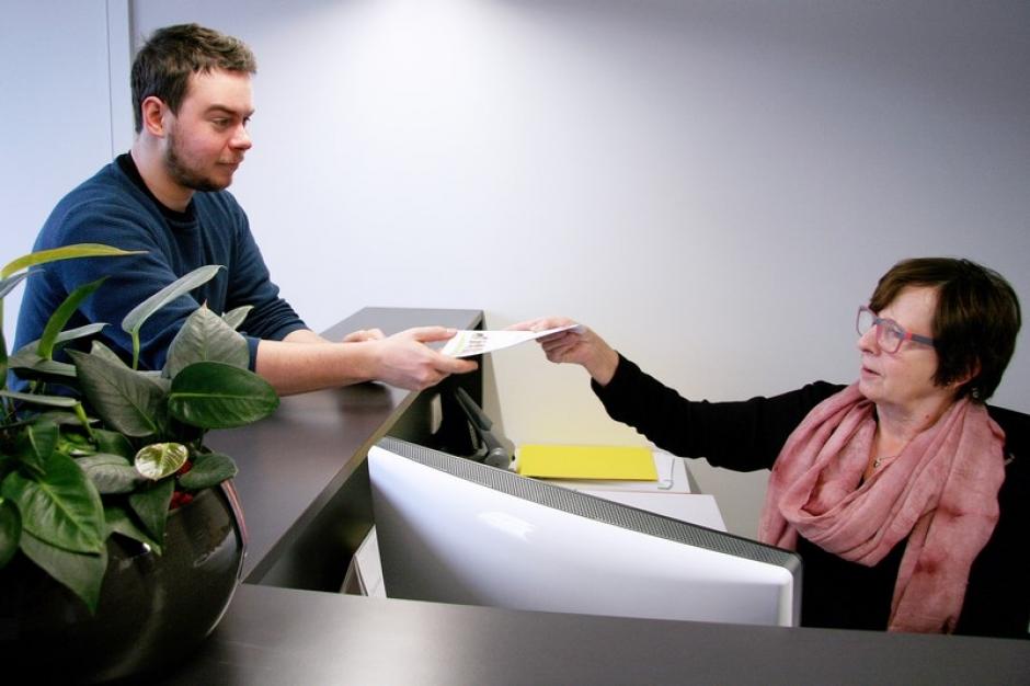 Een klant krijgt enkele documenten mee.