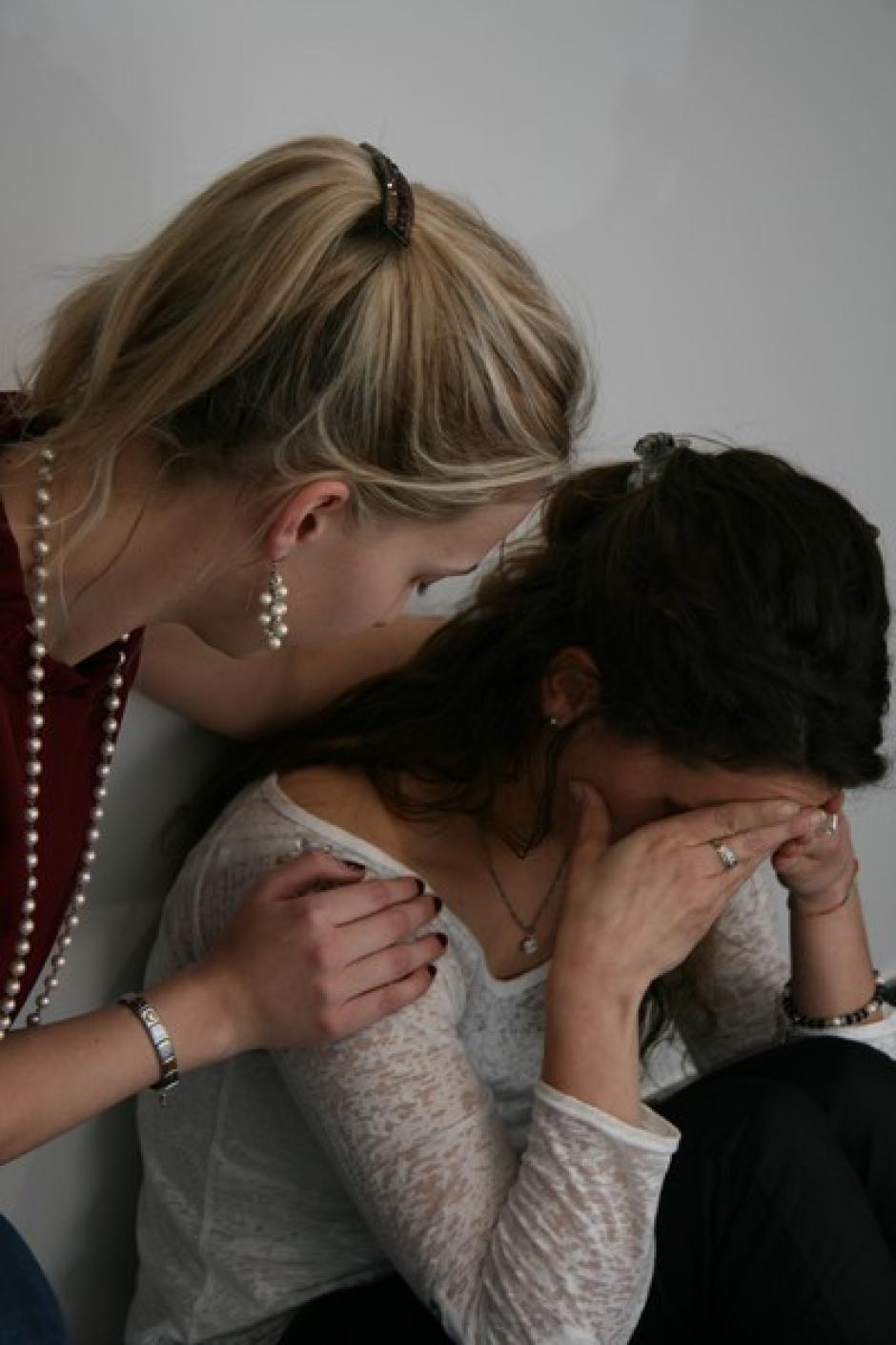 Een vrouw zit met haar hoofd in haar handen. Een andere vrouw troost haar.