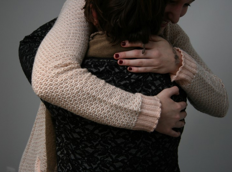 Twee vrouwen omhelzen elkaar al lachend na een sessie relathietherapie bij Faresa